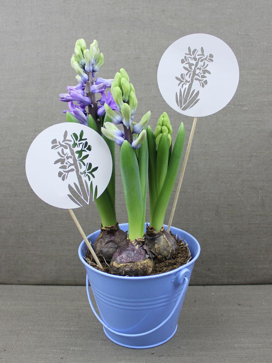Das brauchst Du für einen Blumenstecker: Holzstäbchen. Washi-Tape in einer passenden Farbe und eine geplottete Blüte.