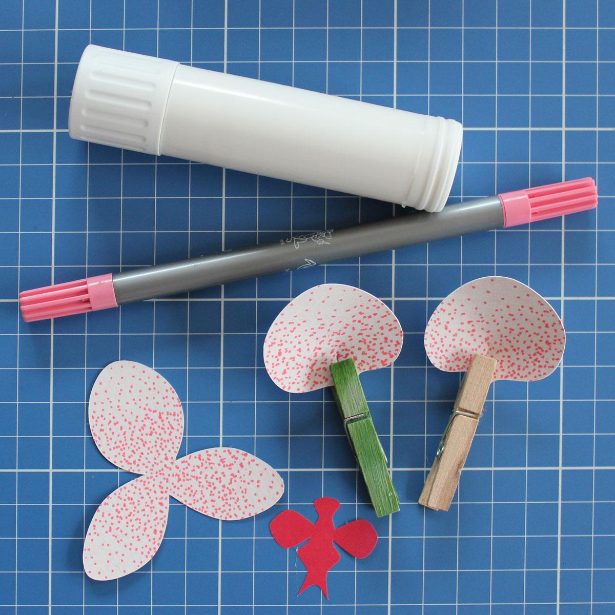 Die bemalten Blüttenblätter am Schlitz übereinander schieben und festkleben. Ich habe diese mit einer kleinen Wäscheklammer zum Trocknen fixiert.