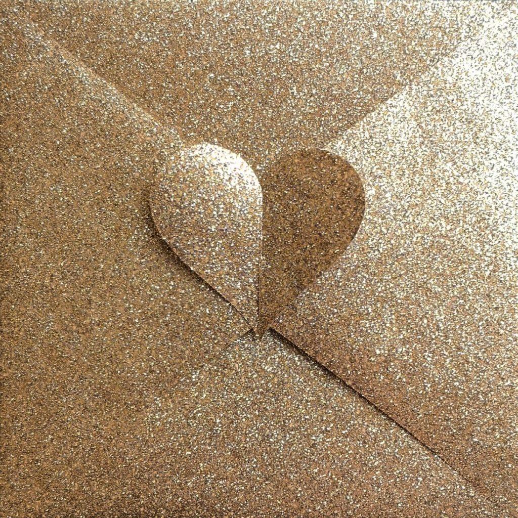 Herzkuvert aus gold-giltzerndem Geschenkpapier