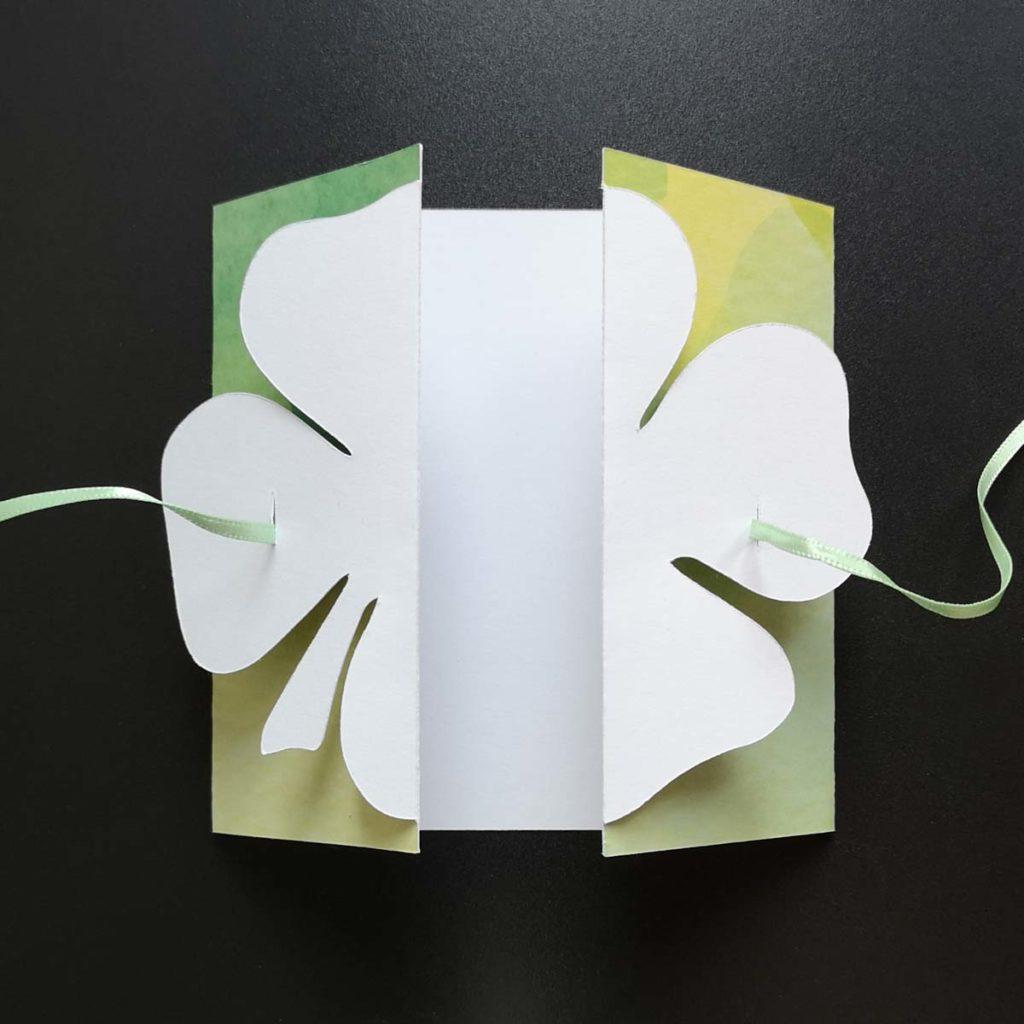 Glückwunschkarte: das Schleifenband um die Karte legen, durch die Schlitze des Kleeblatts durchführen und vorne zur Schleife binden